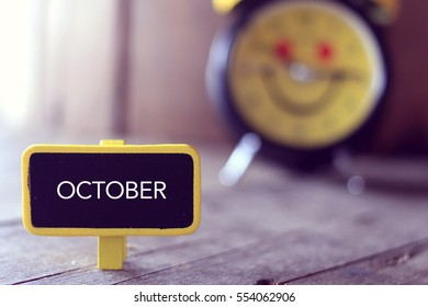 OCTOBER. Words on a small wooden board with vintage tone. business concept