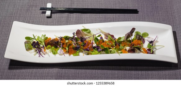 octopus carpaccio with small leaves salad and different types of caviar, fresh and raw food
