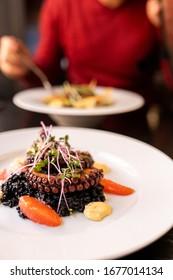 Octopus on white plate in italian restaurant