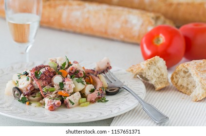 Octopus salad. Background: bread, tomatoes and a glass of white wine.