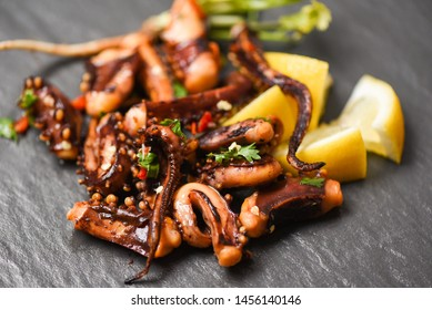 octopus salad with lemon herbs and spices on dark background top view / Tentacles squid grilled appetizer food hot and spicy chilli sauce seafood cooked served on black plate in the restaurant