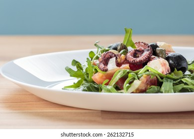 Octopus salad with rucola, olives and feta cheese on white plate with blue background