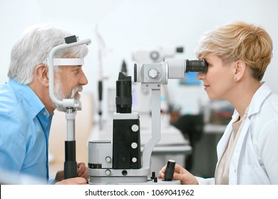 Oculist cheking patient's vision with medical equipment, working in ophthalmilogical laboratory. trying to halp save and imrove old man's vision and health. Doctor is wearing white medical uniform.