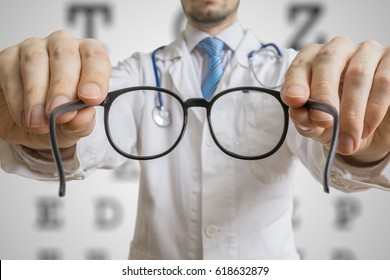 Oculist doctor is offering glasses to a patient. Eye sight testing concept.