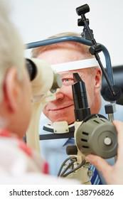 Oculist measuring cornea of elderly man with slit lamp