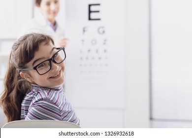 Oculist testing a young patient's eyesight using an eye chart, ophthalmology and eyesight concept