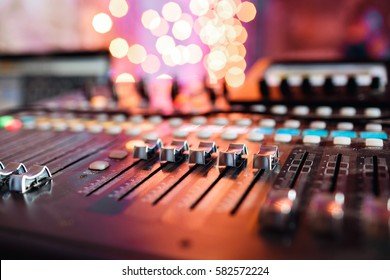 od adjusters and red buttons of a mixing console. It is used for audio signals modifications to achieve the desired output. Applied in recording studios, broadcasting, television.