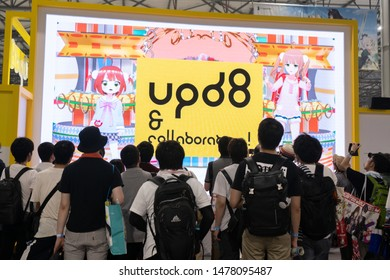 Odaiba, Japan- August 10, 2019: A crowd watches a large screen, during a convention, in Odaiba.