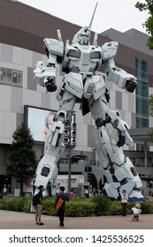 Odaiba, Tokyo / Japan: Jun 2 2019: A size comparison of a tourist to the 1:1 scale unicorn gundam at Odaiba