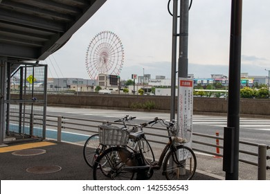 Odaiba, Tokyo / Japan: Jun 2 2019: The Daikanransha ferris wheel in Odaiba seen from a distance from the streets outside a train station entrance.