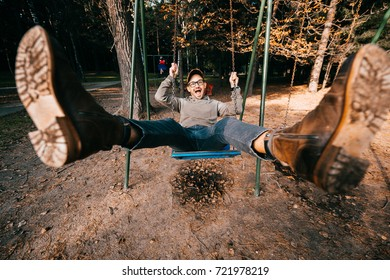 Odd bizarre eccentric people concept. Adult man in vintage expensive fashionable boots riding on a swing in city park on playground for children. Crazy funny idea. Child inside. Legs spread wide