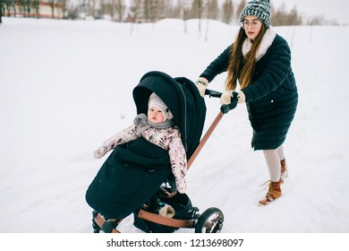 Odd bizzare young beautiful mother pushing baby stroller with her little daughter sitting in it through snowdrifts in winter.  Motherhood difficulties. Funny family. Female parent with child outdoor