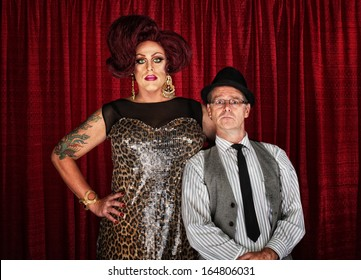 Odd couple drag queen with man at curtain