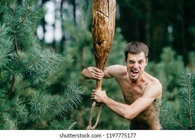 Odd primitive naked man with huge wooden stick hunting in forest. Adult male have fun like crazy psyche with rude club in hands. Expressive excited boy face.  Wild masculine strength. Cruel warrior