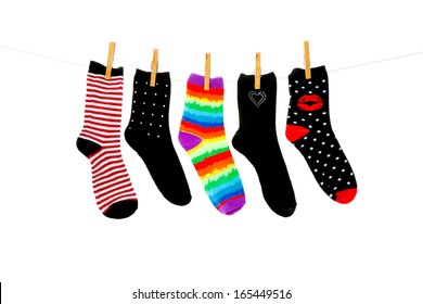 Odd socks whose mates have been lost, hanging on a clothesline.  Shot on white background.