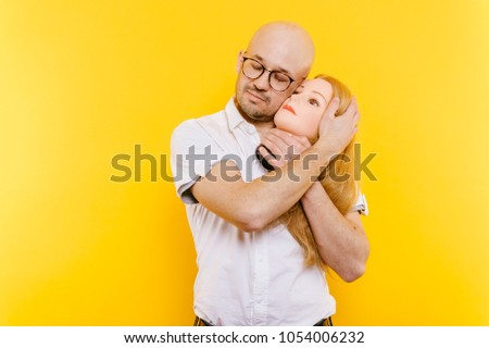 54749ae34f Odd unusual couple in love. Excited bald businessman in glasses holding  pretty girl head.