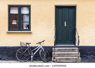 Odense, Denmark; 08 20 2016: Bicycle parked at the door of a home on a street in a Danish city