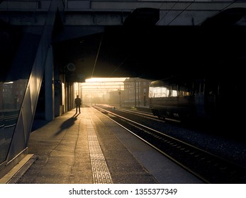 ODENSE, DENMARK - APRIL 1 2019 - Man waiting in the sunrise on a trainstation OBC (Odense Banegaard Center) for a DSB train. The man is only shown as a silhouette with a long shadow behind him