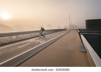 Odense, Denmark - October 5, 2015: Misty morning at Byens bro with a bicycle crossing the bridge.
