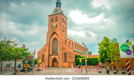 Odense, Funen / Denmark - 07 24 2016: St. Canute's Cathedral in the Hans Christian Andersen birth place city with traditional old Danish timber framing houses in the historic city center.