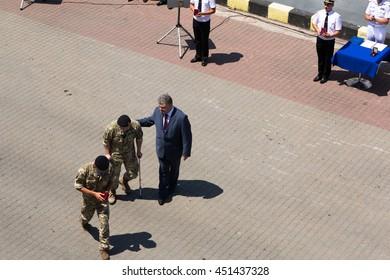 Odesa, Ukraine - July 03, 2016: President Petro Poroshenko helps wounded soldier after award. Navy day celebration.