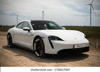 Odesa, Ukraine - May 11, 2020: Porsche Taycan Turbo In a field near wind-driven electric generators. Test drive Porsche Dealership Odesa Porsche Center.