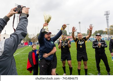 ODESA, UKRAINE - October 21, 2017: Kharkov team celebrates victory in rugby cup of Ukraine. Rewarding athletes. The team thanks coach and throws him into air, shakes coach