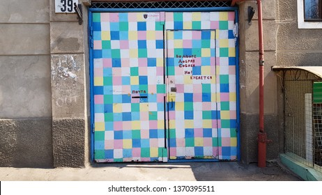 Odessa / Ukraine - 04 05 2019: Colorful squared painted metal gates to courtyard of Odessa Ukraine. Retro gateway of old building. Grunge textures. Bright checkered painted entryway with closed door