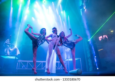 Odessa / Ukraine - 06/03/2018: Sexy girls - go-go dancers in shining metallic dresses perform a show on stage of a night club, assuming erotic positions. Beautiful women dance to techno rave music