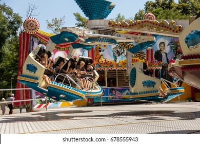 ODESSA, UKRAINE -11 July 2017: Youth entertainments in amusement park. Young friends, boys and girls have fun on exciting rides. Extreme rides - success in summer amusement park. Motion blur