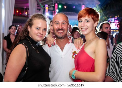 Odessa, Ukraine - 2013 August 26: Ibiza club party. Man and women have fun in night club during concert. People kissing, drinking, make selfy, smiling during night party in night club