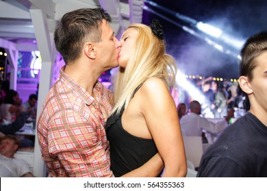 Odessa, Ukraine - 2013 July 7: People make selfy, drink alcohol, dansing, smiling and kissing during concert in night club party. Man and woman have fun at ciub