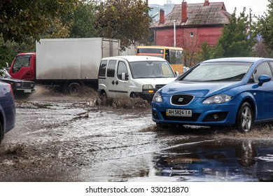 ODESSA, UKRAINE - 21 October 2015: As a result of heavy rains flooded the streets of big puddles. Cars traveling in the rain on a wet road heavily sprayed water and dirt