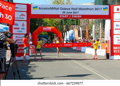 ODESSA, UKRAINE - 25 JUN 2017: Excited female runner crossing the finshline of a marathon. Marathon winner woman at finish. Happy marathon runner finish line.