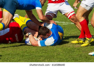 ODESSA, UKRAINE - April 1, 2017: European Rugby Championship national team of Ukraine (Blue) - Portugal (Red). Intense struggle of players in rugby for ball. Dynamic game on green field of stadium