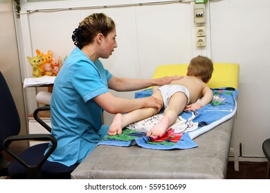 ODESSA, UKRAINE - April 14, 2016: Specialized treatment of children diagnosed with congenital cerebral palsy. Therapists conducting physical exercises and water procedures in pool with sick children