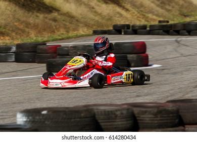 ODESSA, UKRAINE - April 2, 2017: Karting Championship. Drivers in karts wearing helmet, racing suit participate in kart race. Karting show. Children, adult racers karting.