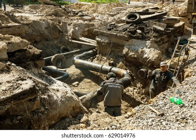 ODESSA, UKRAINE - April 25, 2017: Underground trenches for public utilities. Construction workers dig trenches for laying and installing underground utilities or service pipes on construction site.
