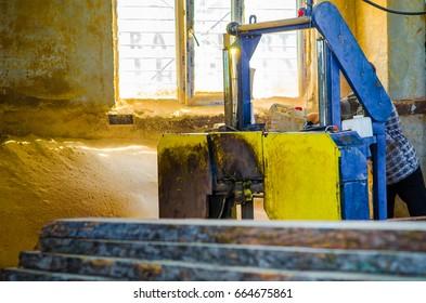 Odessa, Ukraine - APRIL 27, 2017: Worker in workshop using saw machine in woodworking shop of furniture factory.