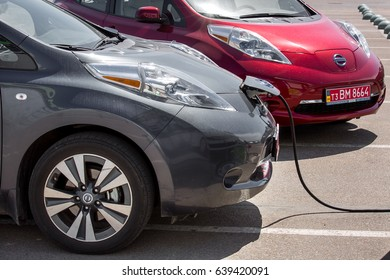 ODESSA, UKRAINE - April 30, 2017: Electric vehicles Nissan leaf are parked on street and  recharge with charging cable.
