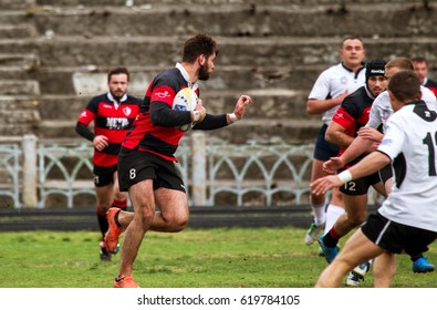 ODESSA, UKRAINE - April 8, 2017: Rugby Championship CREDO Odessa (red) - White wolves of Moldova. Intense struggle of players in rugby for ball. Dynamic game on green field of stadium