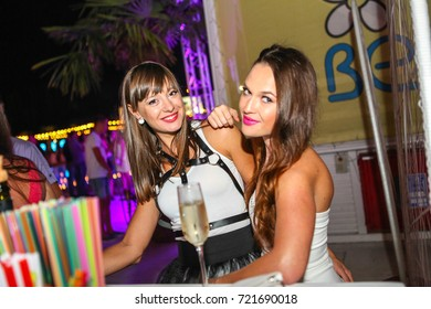 Odessa, Ukraine August 1, 2015: Ibiza night club. People smiling and posing on cam during concert in night club party. Man and woman have fun at club. Boy and girl at night club party