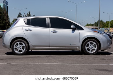 Odessa, Ukraine - August 1, 2017: The Nissan Leaf of Grey Colour electric vehicle parked on the street asphalt parking at shopping center, side view.