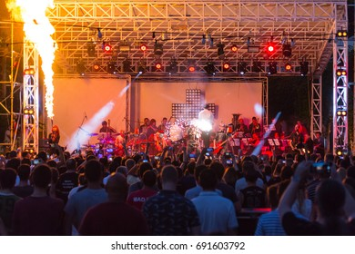 Odessa, Ukraine August 1, 2017: Ramstein cover show. silhouettes of concert crowd in front of bright stage lights. Fans at concert, night party, audience raising hands up