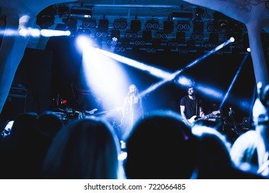 Odessa, Ukraine August 10, 2014: Ibiza Night club dj party people enjoy of music dancing sound with colorful light with Smoke Machine and lights show. Hands up in the earth.