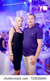 Odessa, Ukraine August 13, 2014: Ibiza night club. People smiling and posing on cam during concert in night club party. Man and woman have fun at club. Boy and girl at night club party