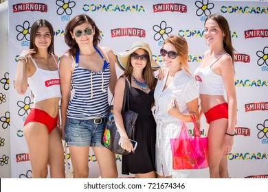Odessa, Ukraine August 2, 2014: Party vodka Smirnoff. Beautiful glamorous men, women, boys and girls posing for camera on background wall of vodka brand Smirnoff during elitny Laksheri partying