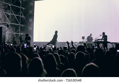 Odessa, Ukraine August 20, 2015: Rear view of crowd with arms outstretched. cheering crowd at rock concert. silhouettes of concert crowd in front of bright stage lights. audience raising hands up