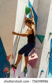 ODESSA, UKRAINE - August 20, 2017: Sports people are trying to climb vertical wall. Athletes climbers compete on an artificial stone rock. Mountaineering. Rock Climbing on Imacette vertical wal
