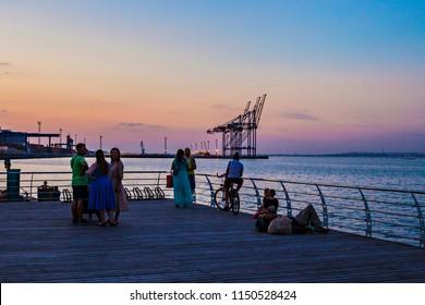 ODESSA, UKRAINE - August 2018: People on the wooden pier against Odessa port cranes during sunset, Ukraine